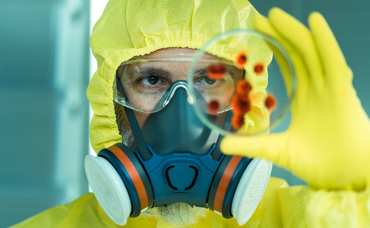 Man in hazmat suit with a petri dish
