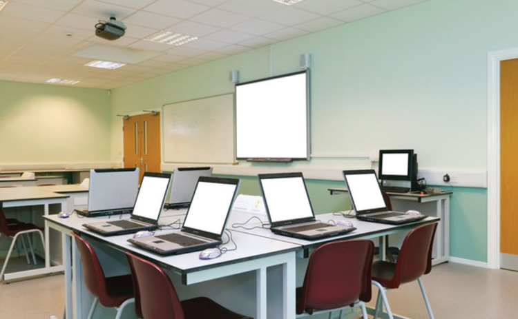 An empty classroom with a white board and a number of laptops