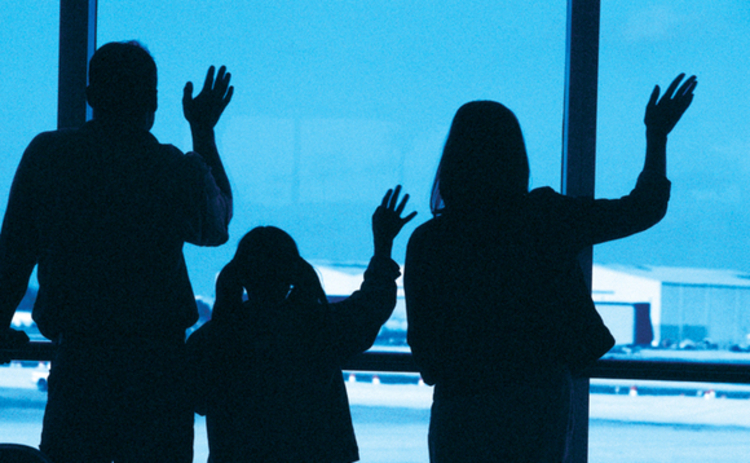 Family waving goodbye at an airport in silhouette