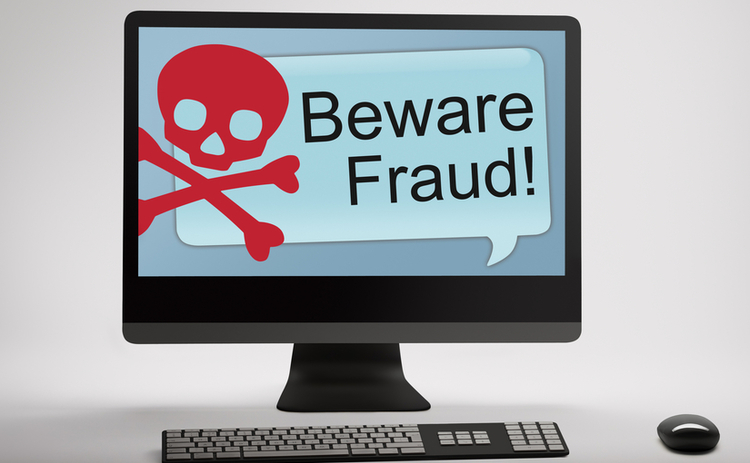 A desktop monitor with 'Beware Fraud' on the screen