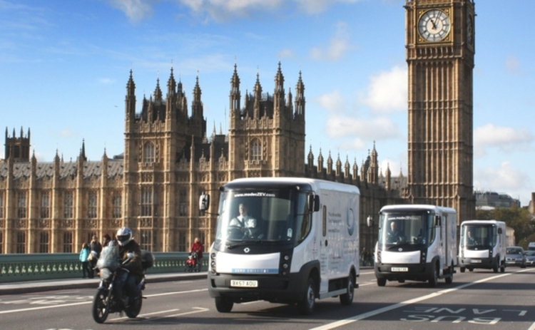 Modec electric vehicles driving past Parliament and Big Ben