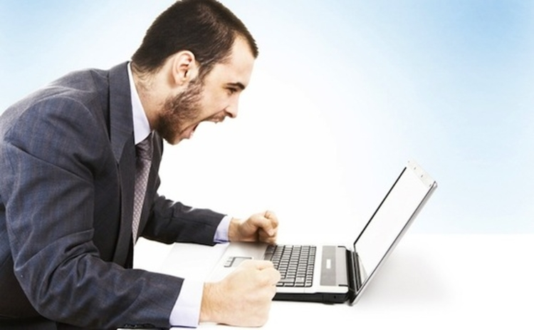 An angry man shouting at a laptop