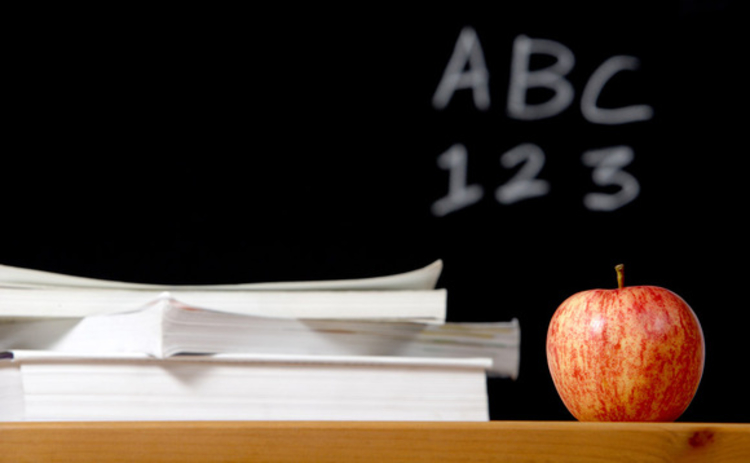 Blackboard and desk with an apple and books on it