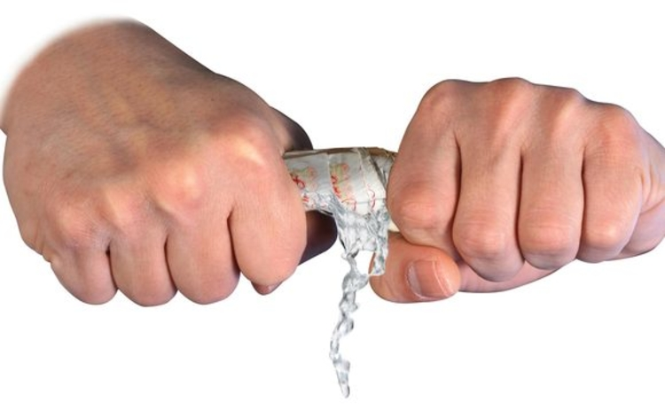 Twisting fifty pound notes between hands until water is wrung out