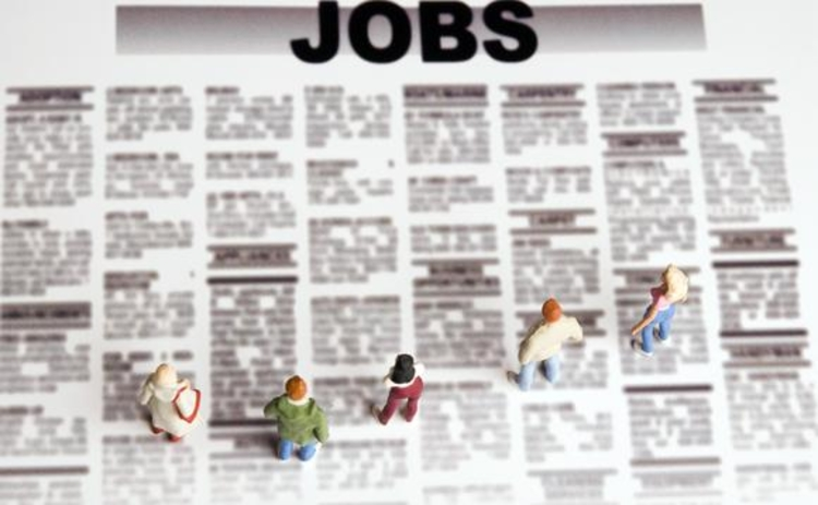 Figurines standing on the jobs paper representing career choice