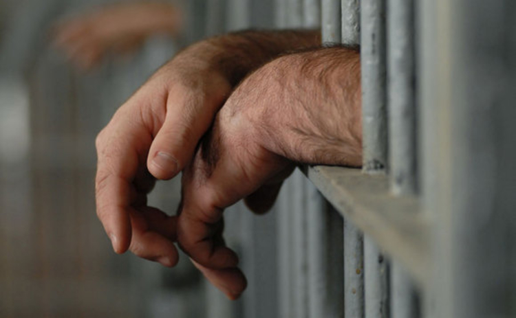 A man's hands sticking through prison bars