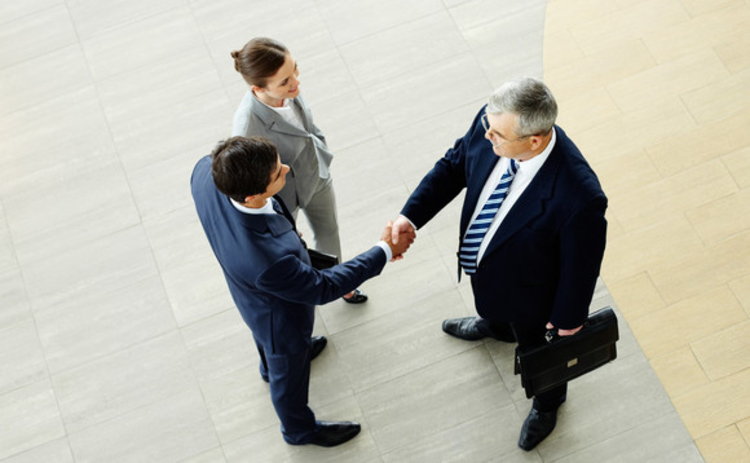 Three businesspeople meet and shake hands